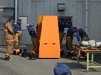 写真:訓練火災指令を受け、隊員が防火衣を着装している様子