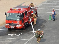 写真:現場到着し、隊員が消火用ホースを延長している様子