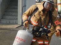 写真:隊員が模擬火災建物から危険物品を排除している様子